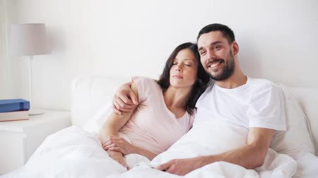 evli : happy couple watching tv in bed at home