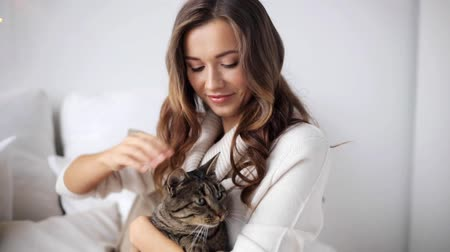 kotki : happy young woman with cat in bed at home