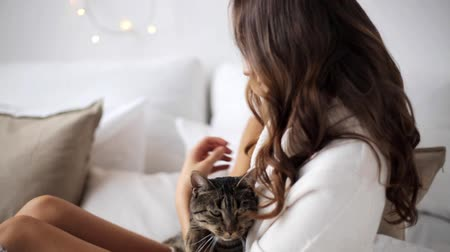 pisi : happy young woman with cat in bed at home