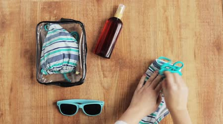 stuff bag : hands packing beach accessories to bag