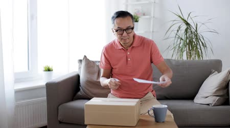 tektura : man reading invoice and opening box at home Wideo