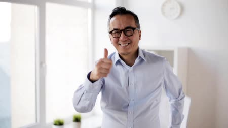 jóváhagyás : happy businessman showing thumbs up at office