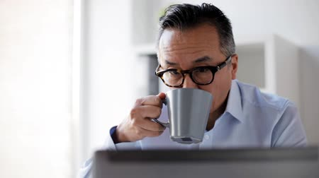 business man : businessman with laptop drinking coffee at office