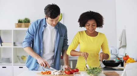 culinária : happy couple with tablet pc cooking food at home