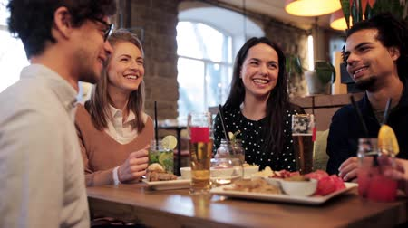 bebida alcoólica : happy friends clinking drinks at bar Stock Footage