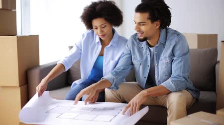 blueprint : happy couple with blueprint and boxes at new home Stock Footage