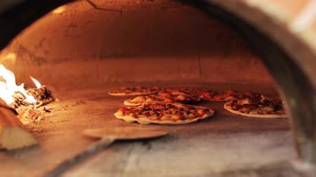 forno : peel placing pizza baking in oven at pizzeria