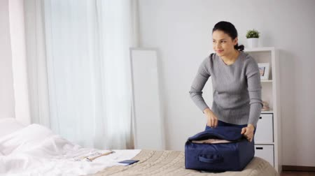 zsák : woman packing travel bag at home or hotel room