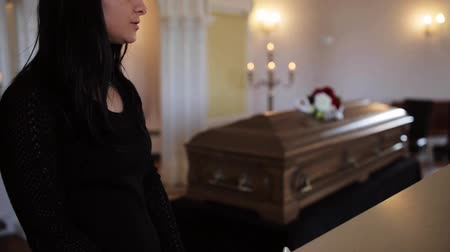 trumna : sad woman and coffin at funeral in church