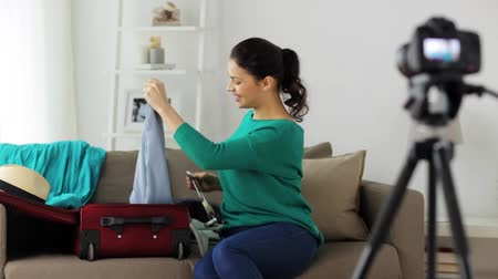 латинский : woman with travel bag recording video at home