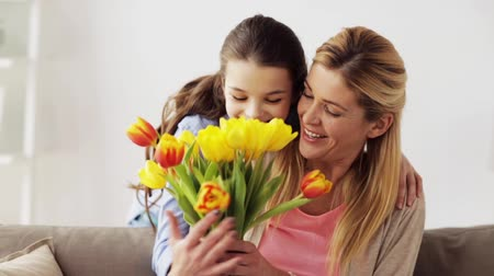 tulipany : happy girl giving flowers to mother at home