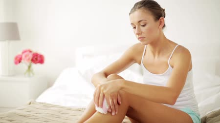 epilating : woman with epilator removing hair on legs at home