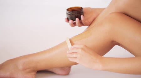 estância termal : beautiful woman applying depilatory wax to her leg Vídeos