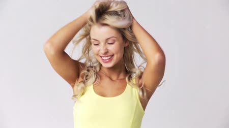 blond vlasy : happy smiling beautiful young woman touching hair Dostupné videozáznamy