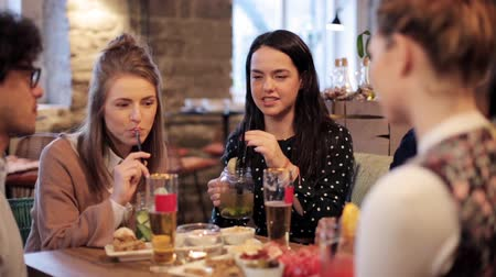 snack : happy friends eating and drinking at bar or cafe Stock Footage