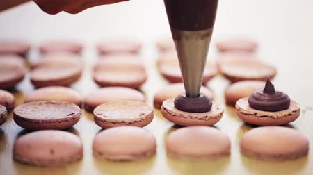 culinária : chef with injector squeezing filling to macarons Vídeos