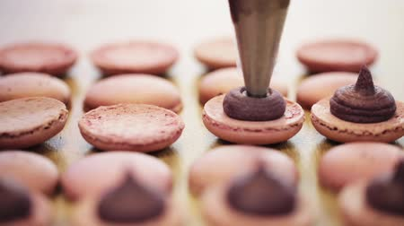 chef cooking : injector squeezing filling to macarons