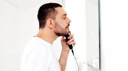 barbear : man shaving beard with trimmer at bathroom