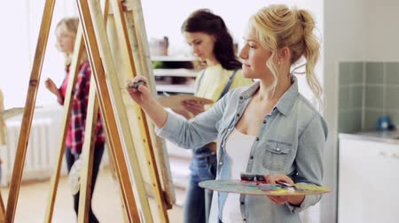 artistas : women with brushes painting at art school
