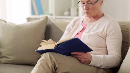 yaşlanma : senior woman in glasses reading book at home Stok Video