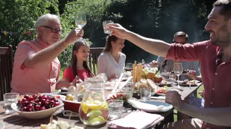 három ember : happy family having dinner or summer garden party Stock mozgókép