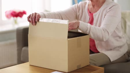 tektura : senior woman opening parcel box at home