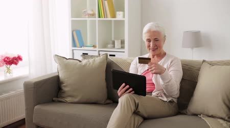 cash free : senior woman with tablet pc and credit card
