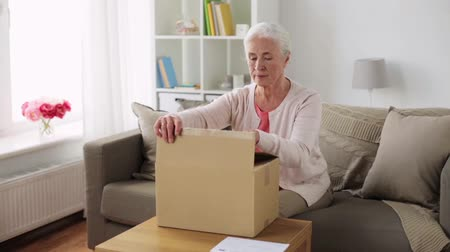 balík : senior woman opening parcel box at home