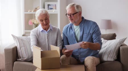banknoty : senior couple with parcel and delivery note