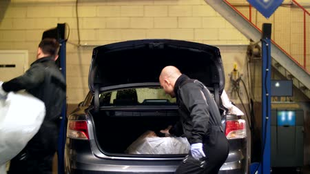 changer : mechanics taking tires out of car trunk at service Stock Footage