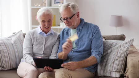 cash free : happy senior couple with tablet pc and credit card