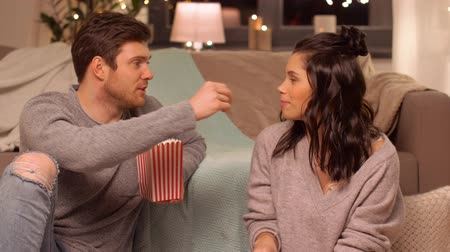 feed on : happy couple eating pop corn at home