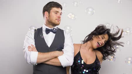 züppe : happy woman and bored man at party with bubbles Stok Video