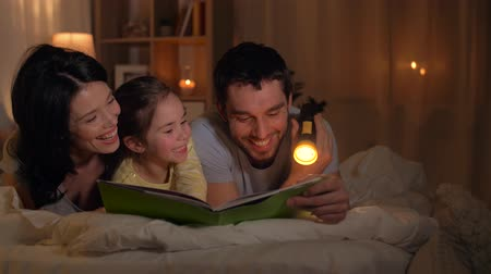 zseblámpa : happy family reading book in bed at home Stock mozgókép