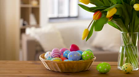 koszyk wielkanocny : colored easter eggs in basket and flowers at home
