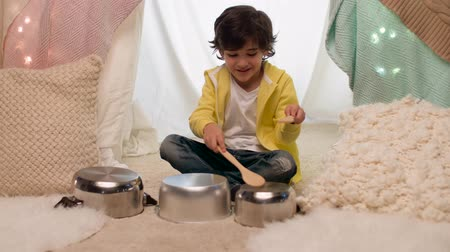 барабаны : boy with pots playing music in kids tent at home Стоковые видеозаписи