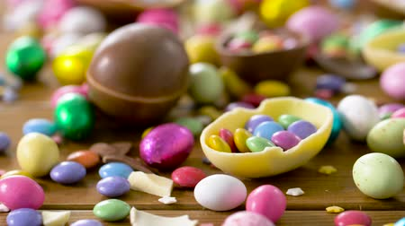 нездоровое питание : chocolate easter eggs and drop candies on table Стоковые видеозаписи