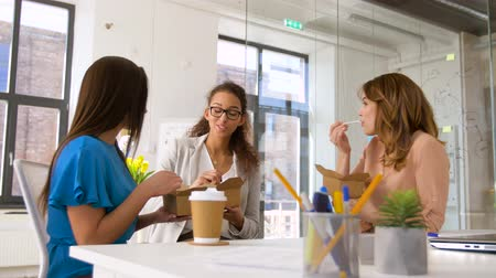 wok : happy businesswomen eating take out food at office Stock Footage