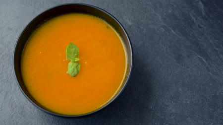porce : hands putting bowl of pumpkin cream soup on table