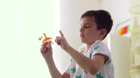 pre hispanic : happy little boy playing with airplane toy at home Stock Footage