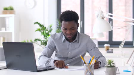 afro americana : businessman with laptop and papers at office