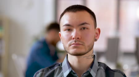 machos : asian man with tattoo and ear tunnel at office