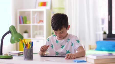 schoolkid : smiling boy with tablet pc sitting at home desk Stock Footage