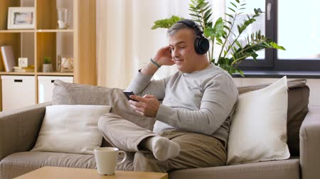 прослушивание : man with smartphone and headphones at home Стоковые видеозаписи