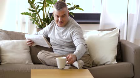 hot news : man reading newspaper and drinking coffee at home