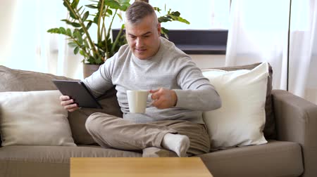 hot news : man with tablet pc sitting on sofa at home