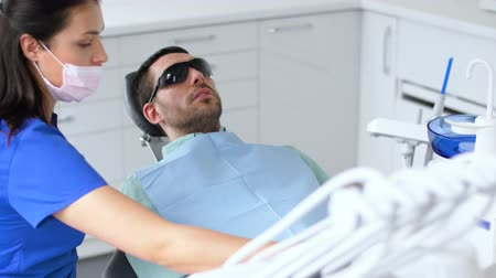 stomatological : dentist adjusting patient chair at dental clinic