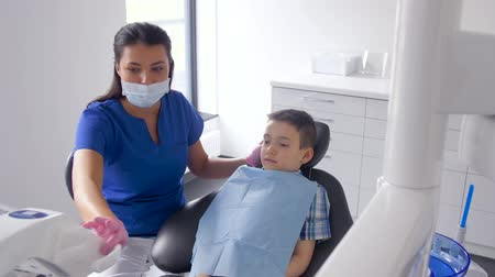 ajustando : female dentist with kid patient at dental clinic