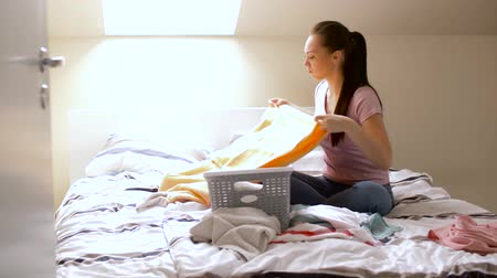 кровать : woman or housewife sorting laundry at home