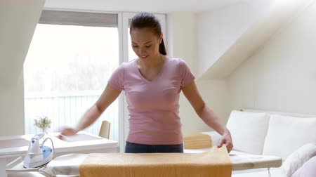 servant : woman or housewife ironing towel by iron at home